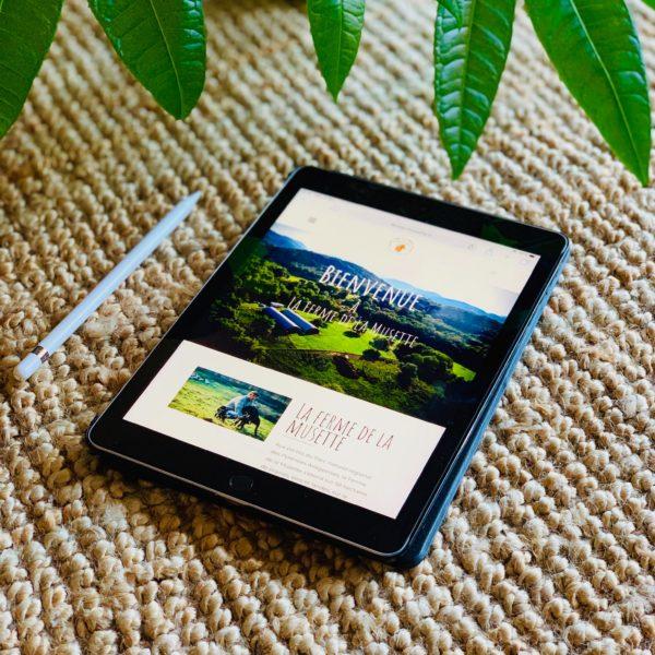 tablette ta ctile avec le site web La ferme de la musette, une plante verte en fond sur du jon de mer