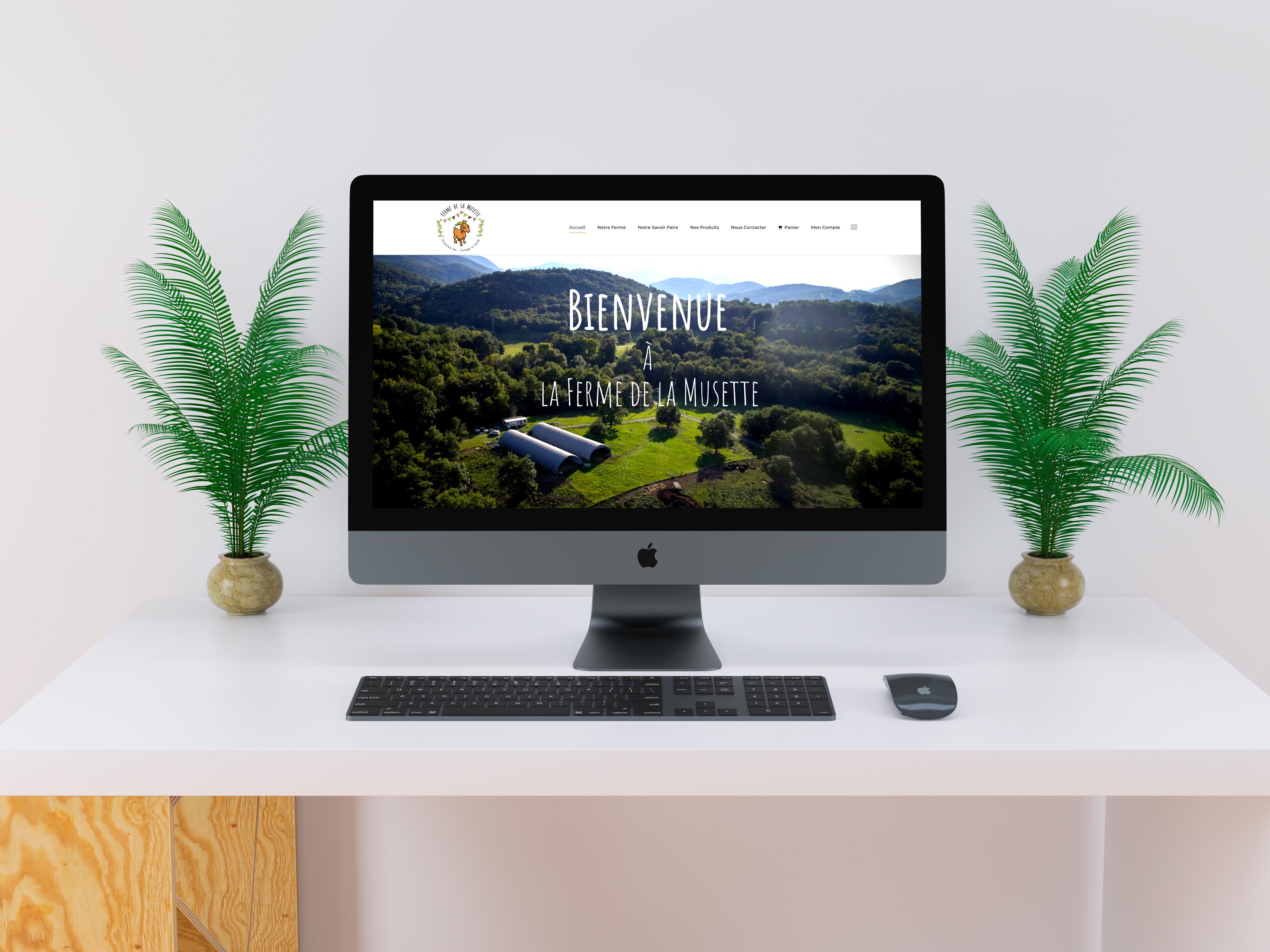 ordinateur avec une site internet d'une ferme sur un bureau blanc et deux plantes