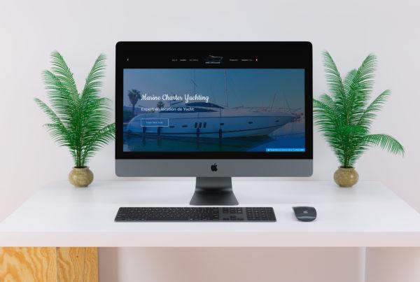 ordinateur avec une site internet de bateau sur un bureau blanc et deux plantes