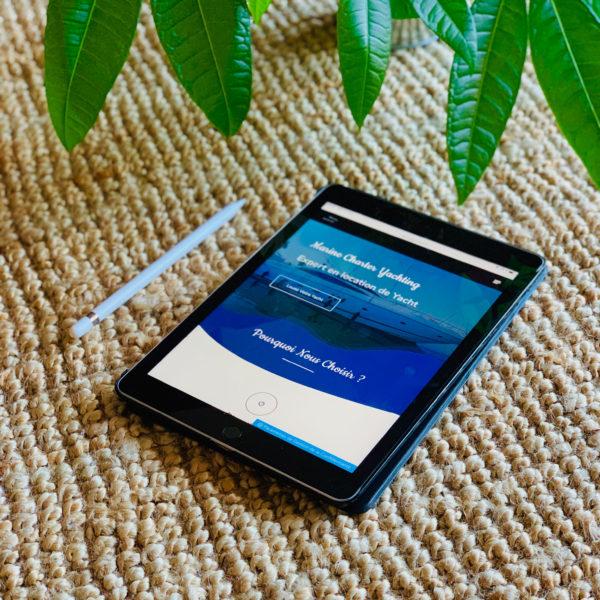 tablette tactile avec le site Marine charter yachting, une plante verte en fond sur du jon de mer